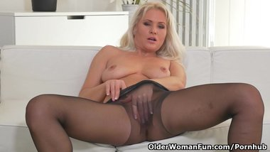 Blonde milf Kathy peels off her black nylons and plays